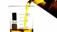 Pouring yellow liquid into Beaker