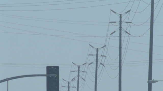 Power poles w/ multiple extensions in smog air TD Passing Flores Street Sweetzer Avenue signs WS Oncoming stopped traffic Air pollution fossil fuel...