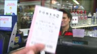 WGN Powerball Hits $425 Million Cashier Selling Powerball Tickets on August 06 2013 in Chicago Illinois