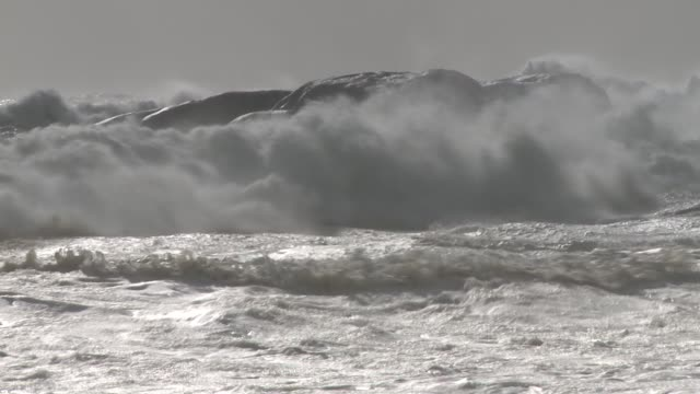Powerful ocean waves crash into a coastal rock. Available in HD.