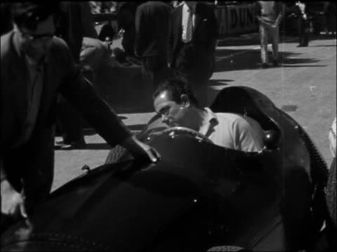 Practice session at Monaco Grand Prix MONACO Monte Carlo EXT Racing cars in paddock Car engine worked on by mechanic Bonnet being put on car Cars...