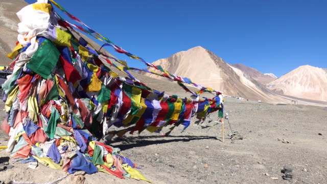 Prayer flags at Pangong Lake with mountain and blue sky, Ladakh, North India