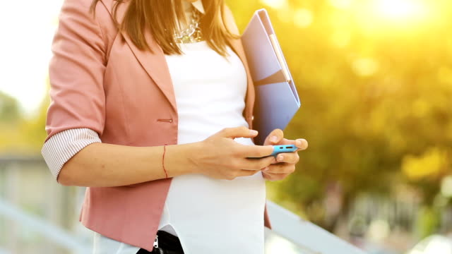 Pregnant business woman using smartphone