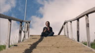 Pregnant female sitting on stairs with telephone outdoors
