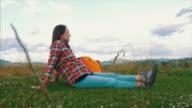 Pregnant tourist woman sitting on grass