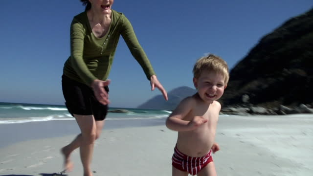 SLO MO MS WS Pregnant woman and boy (2-3) running on beach, Cape Town, South Africa