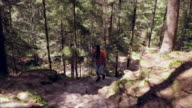 Pregnant woman carefully climbing on mountain path
