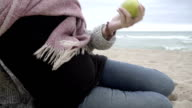 M/S TU pregnant woman eating an apple in the beach (winter)