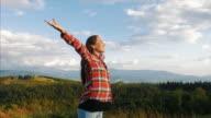 Schwangere Frau genießt die Sonnenstrahlen am Gipfel des Berges