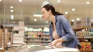 Pregnant woman looking at ready meal in grocery store
