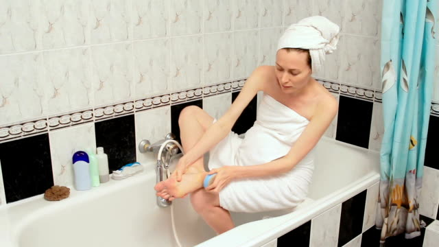 Pregnant woman scrubbing foot by pumice