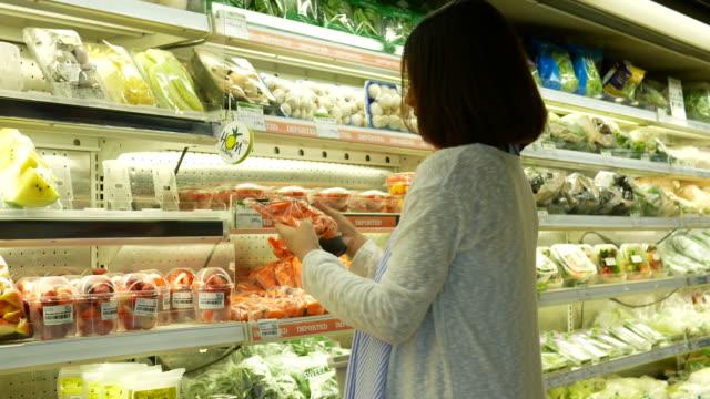 zwangere vrouw winkelen in de supermarkt en het gebruik van de telefoon