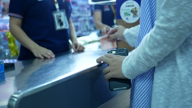 pregnant woman spending money at cashier counter store