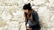 Pregnant woman standing near the city wall