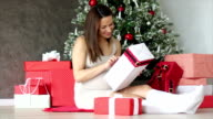 Pregnant woman under Christmas tree holding present gift box