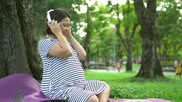 Zwangere vrouw hoofdtelefoon met haar baby.