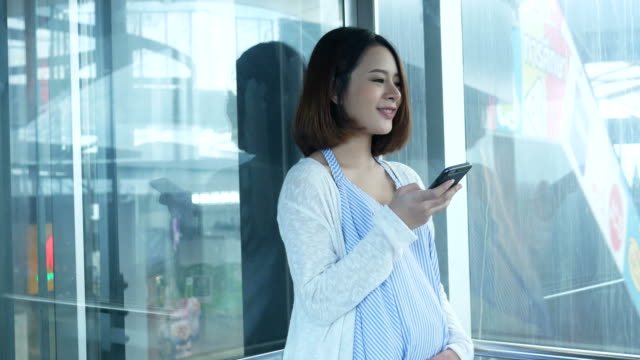 pregnant woman using smartphone in elevator