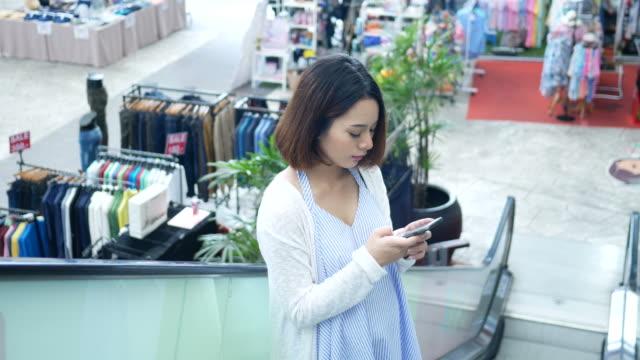 zwangere vrouw met smartphone op roltrap