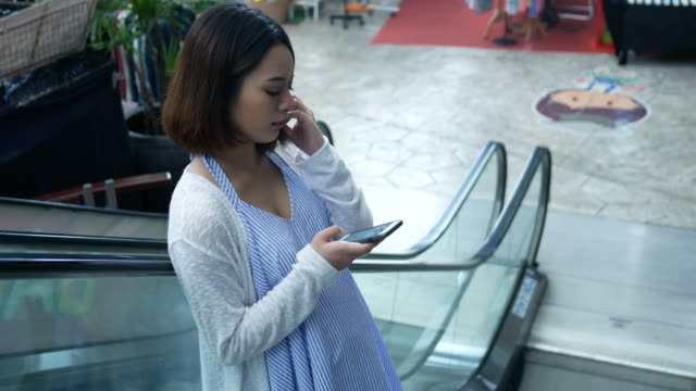 pregnant woman using smartphone on escalator