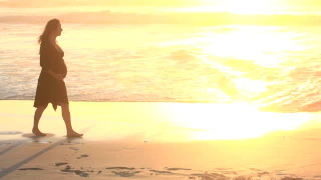 Schwangere Frau zu Fuß am Strand bei Sonnenuntergang