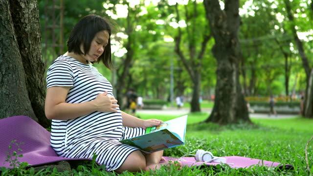 Zwangere vrouw met boek zit in het park en het lezen van het boek aan haar baby.