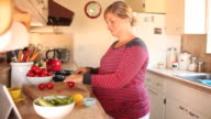 A pregnant women eating and drinking in healthy ways inside of her kitchen.