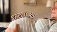 A pregnant women using blocks to spell the word 2016 on her stomach.