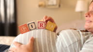 A pregnant women using blocks to spell the word GIRL on her stomach.
