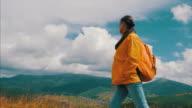 Schwangere junge Frau, die zu Fuß in den Bergen