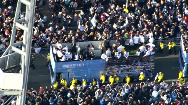 Manchester City victory parade Aerials AIR VIEWS Manchester City bus along road past fans during victory parade / buses arriving at MEN Arena...
