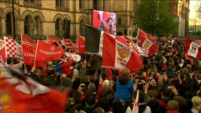 Manchester United victory parade GVs parade ENGLAND Manchester Albert Square EXT Crowd in front of stage waving flags and banners and giant screen on...