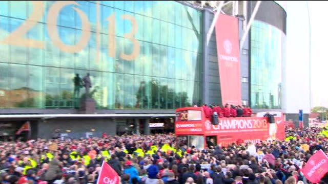 Manchester United victory parade Opentop bus More Manchester United players celebrating on bus including Robin van Persie waving scarf around head /...