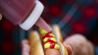 Preparing Hot Dog with Mustard and Ketchup