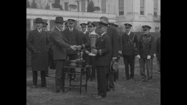 US Pres Calvin Coolidge standing with US Navy Lt James Dyer holding silver Herbert Schiff Trophy awarded for the most flight hours without accident...