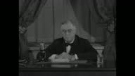 US Pres Franklin D Roosevelt sitting at desk speaks into microphone regarding Nazi domination of Europe 'never before since Jamestown and Plymouth...