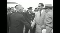Pres Harry Truman standing on tarmac at airport with wife Bess people standing around / Truman walking along people around him man comes up to him...