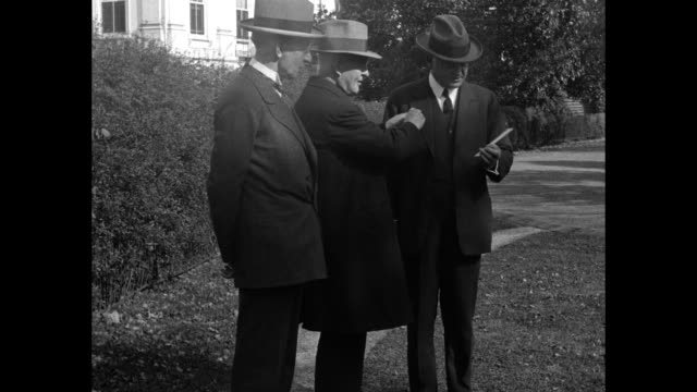 Pres Herbert Hoover and others walking past trellis and passing camera top corner of White House / VS Hoover presented with lapel button as Charles...