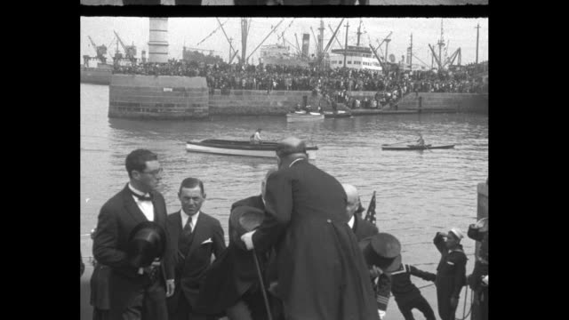 US Pres Herbert Hoover steps from motor launch at dock with large ship beyond / he walks with group of dignitaries and enters convertible conveyance...