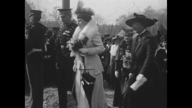 MS Pres Woodrow Wilson and wife Edith walk with VIPs in between rows of soldiers at attention and women in the emergency corps towards camera tents...