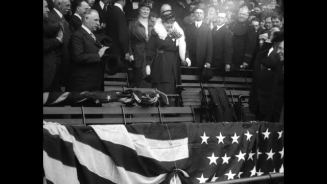Pres Woodrow Wilson walking down aisle with wife Edith behind him they sit in front row with another official and his wife / Wilson stands and is...