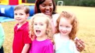 Preschool children in park with two women, bounce house