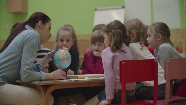 4K: Preschool teacher and children learning geographic in classroom.