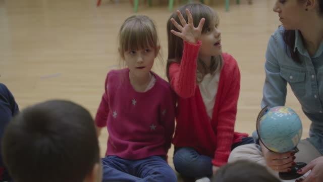 4K: Preschool leraar en kinderen zitten op de vloer in de klas.