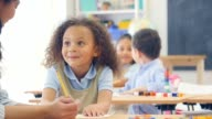 Preschool teacher helps cute mixed race schoolgirl in class