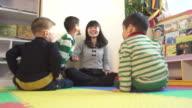 preschool teacher relax with children in classroom,slow motion
