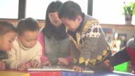preschool teacher teaching children in classroom