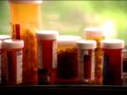 Prescription pill bottles sit on a window sill.