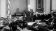 President Eisenhower walks into press conference and all the reporters stand / shots of various reporters taking hand written notes / Eisenhower...