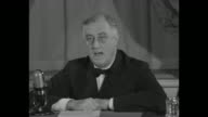 President Franklin D Roosevelt sitting at desk speaking into microphone re promoting aid to US allies to fight against Axis threat throughout world...