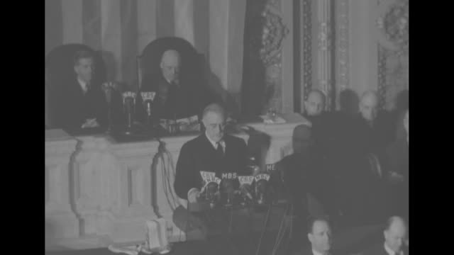 President Franklin D Roosevelt with Speaker of the House Sam Rayburn and Vice President Henry A Wallace behind him in well of the House of...